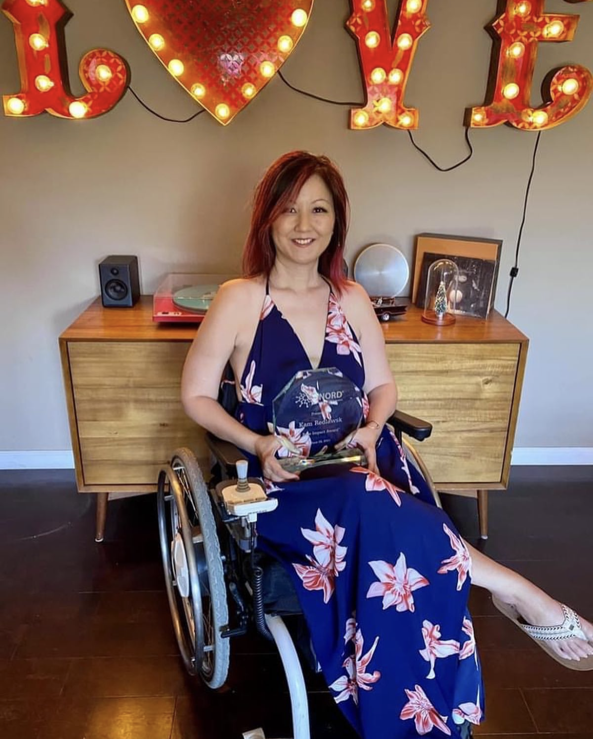 Woman in wheelchair holding award